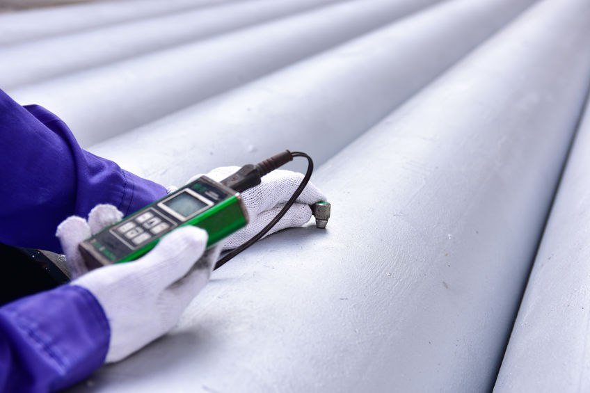 Inspector measuring thickness the pipe with UTM